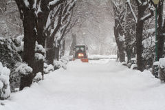 Orange tractor driving down snow in a park alley Royalty Free Stock Image