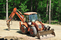 Orange tractor modified as excavator Royalty Free Stock Images