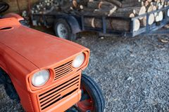 Orange tractor next to a trail loaded with logs Stock Photo