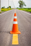 Orange traffic cone on center of country road Stock Photography