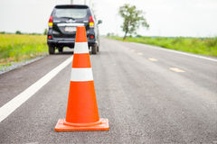 Orange traffic cone on country road Stock Photography