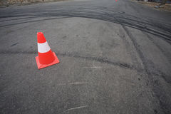 Orange traffic cone and skid marks Royalty Free Stock Image