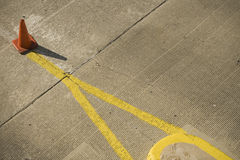 Orange traffic cone and yellow lines Royalty Free Stock Photo