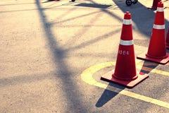 Orange trafikkottar i utomhus- parkeringsplats Royaltyfri Foto