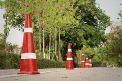 Orange trafikkottar på vägen på parkera Arkivfoton