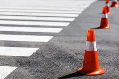 Orange trafikkottar som i rad står nära gångarekorset Royaltyfri Foto
