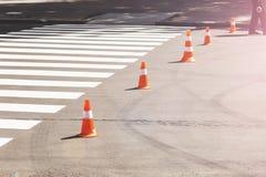 Orange trafikkottar som i rad står nära gångarekorset Arkivbild