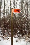 An orange trail marker sign along a hiking path.  stock images