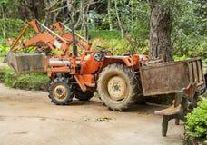 Orange traktor med en släp och stora hjul Royaltyfria Foton