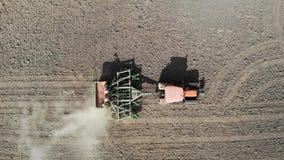 Orange Traktor pflügt das Feld Schattenbild des kauernden Geschäftsmannes stock footage