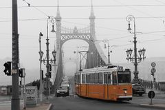 Orange tram on a black white cityscape background. Bridge in the fog. stock image