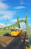 Orange tram on the Liberty bridge in Budapest, Hungary Royalty Free Stock Images