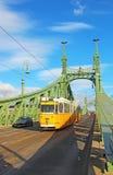 Orange tram on the Liberty bridge in Budapest, Hungary Royalty Free Stock Images