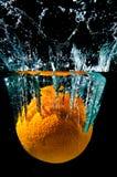 Orange Tropfen in Wasser Stockbild
