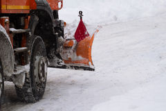 Orange truck with plough driving down snow on a city street Stock Images