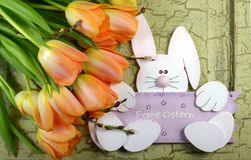 Orange tulips and a easter bunny on an green vintage background stock image