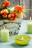 Orange tulips in wooden basket and green lit cadles Stock Photos