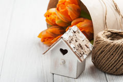 Orange tulips, wooden heart shape bird house and twine. Easter greeting card with orange tulips, wooden heart shape bird house and twine. Space for text. country stock photo