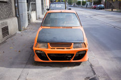 Orange tuned car abandoned on the sidewalk Royalty Free Stock Photography