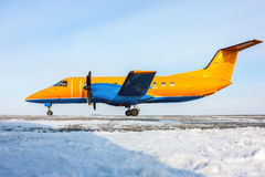 Orange turboprop aircraft. On the winter airfield Royalty Free Stock Photos