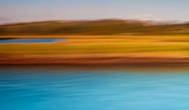 Orange and Turquoise Abstract of Water and Land. Abstract of dark orange grass and turquoise water with sky in background Royalty Free Stock Images