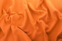 Orange tyg som en bakgrund Arkivfoto