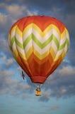 Orange u. gelber Heißluftballon, der unter Wolken schwimmt Stockbild