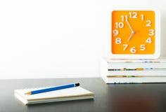 Orange Uhr auf Staplungsbuch mit weißem Kopienraum Stockbild