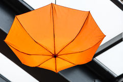 Orange umbrella hanged by roof Stock Image
