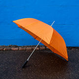 Orange Umbrella on Sidewalk in front of Blue Wall Stock Photography