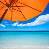 Orange umbrella on  tropical beach. Red umbrella on  tropical beach. Travel  background Royalty Free Stock Photos