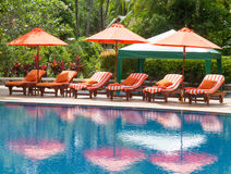 Orange umbrellas and bed at the pool. Stock Photos
