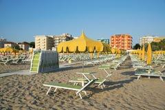 Orange umbrellas and chaise lounges on the beach of Rimini in It. Aly - the destination in the Adriatic coast of Emilia-Romagna stock image