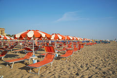Orange umbrellas and chaise lounges on the beach of Rimini in It. Aly - the destination in the Adriatic coast of Emilia-Romagna royalty free stock photo