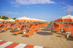 Orange umbrellas and chaise lounges on the beach of Rimini in It Royalty Free Stock Images