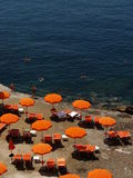 Orange umbrellas and people. Bright orange umbrellas on a small beach with a deep blue sea for a strong chromatic contrast. This place is in Italy, near Naples royalty free stock photography