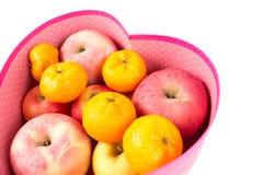 Orange und Apfel mischten in der Herz-förmigen Geschenkbox auf Weiß lizenzfreies stockbild