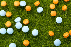Orange und blaue Pillen, die auf dem grünen Gras verschüttet werden Lizenzfreie Stockfotos