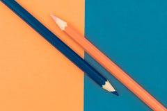 Orange und dunkelblaue farbige Bleistifte und Papier Stockfotos