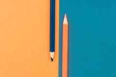 Orange und dunkelblaue farbige Bleistifte und Papier Lizenzfreie Stockfotos