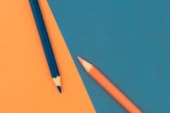 Orange und dunkelblaue farbige Bleistifte und Papier Stockfoto