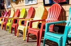 Orange und gelbe Adirondack-Stühle Lizenzfreie Stockfotos
