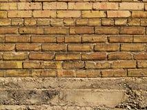 Orange und gelbe Backsteinmauer über Beton Stockfotografie