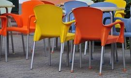 Orange und gelbe Plastikstühle Stockfoto