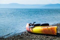Orange und gelber Kajak mit Rudern auf dem Seeufer lizenzfreies stockbild