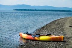 Orange und gelber Kajak mit Rudern auf dem Seeufer stockfoto
