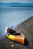 Orange und gelber Kajak mit Rudern auf dem Seeufer lizenzfreie stockfotografie