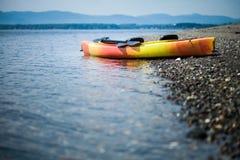 Orange und gelber Kajak mit Rudern auf dem Seeufer stockfotografie