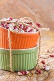 Orange und grünes cocotte mit Bohnen Stockfoto