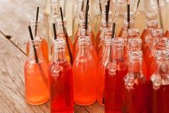Orange und rote Farbauffrischungsgetränke innerhalb der kleinen Flaschen mit Rohren auf einem Holztisch in einem Café im Freien stockfoto